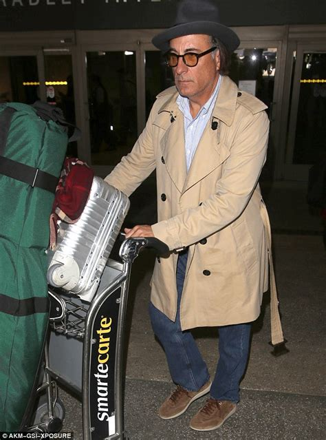 Andy Garcia wheels an enormous bag of golf clubs as he